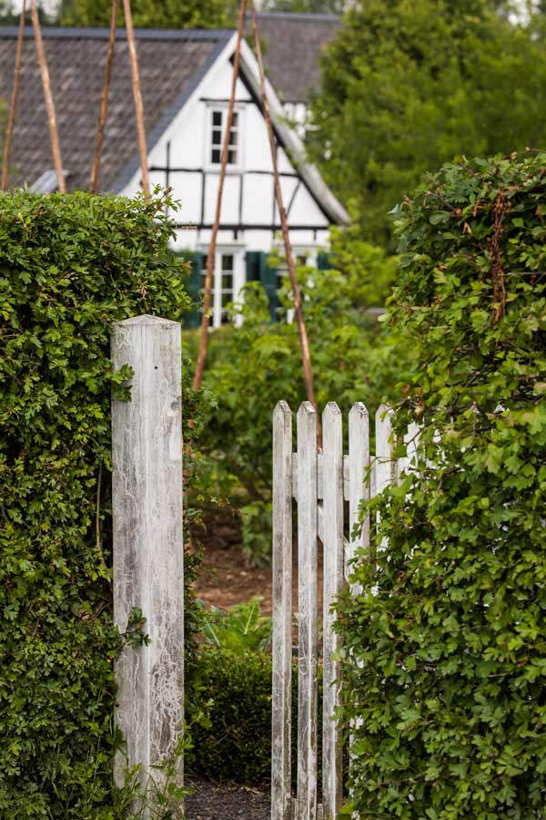 Weißer Gartenzaun vor Fachwerkhaus